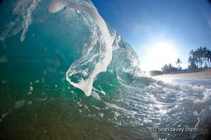 An ocean wave crashing onto beach at Monster Mush, north shore, Oahu, Hawaii